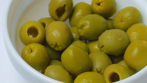 Pickled green olives in a bowl on a white backgrou Footage