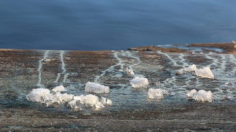 Pieces Of Ice Melting On A Lakeside Rock stock footage