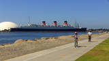 Mother Daughter Ride Bikes Near Queen Mary Ship stock footage