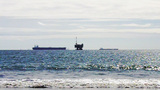 Oil Well Platform And Cargo Ships Off Beach stock footage