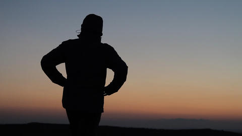 Silhouetted man standing in sunset Footage