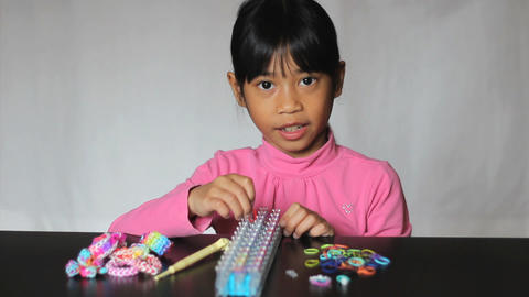Asian Girl Enjoys Making A Bracelet On Her Loom Footage