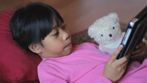 Cute Asian Girl Reads Story To Teddy Bear Footage