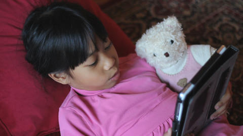 Eight Year Old Girl Reads Story To Teddy Bear stock footage
