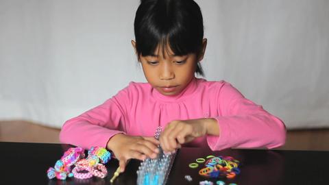 Girl Making Colorful Bracelet On Her Loom Footage