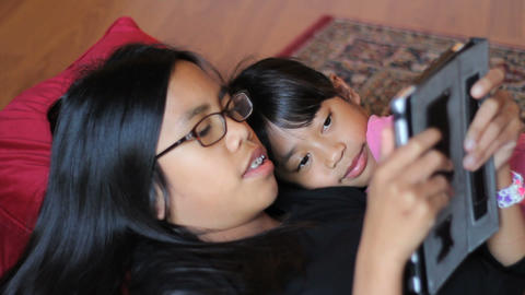 Girl Reads Story To Little Sister Off Tablet Footage