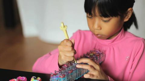 Girl Uses Hook On Her Bracelet Loom Footage