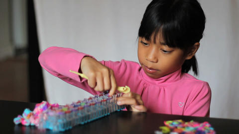Girl Works On Colorful Bracelet On With Her Loom Footage