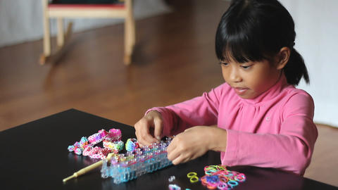 Little Girl Making Rainbow Bracelet On Her Loom Footage