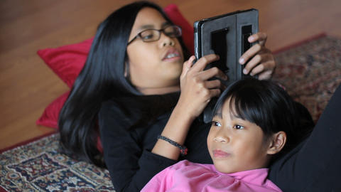 Teenage Girl Reads Book To Little Sister On Tablet Footage