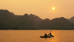 Kayakers Passing By As Sun Sets Behind Mountains I stock footage