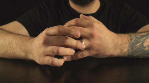 Young Male Putting A Ring On His Finger Front-Shot Footage