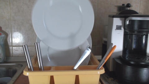 Man Puts Dishes In A Dish Stand Front Shot Footage