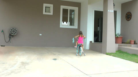 Little girl dropping her bicycle in front of her h Footage