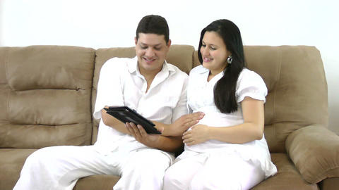 Prospective Parents Looking At Tablet Pc On Sofa I stock footage