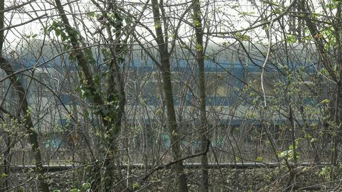 4K Train behind Trees Industrial Area 3 Footage