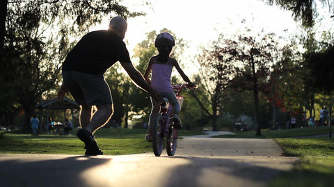 Father Helping Young Daughter Ride Her Bike Footage