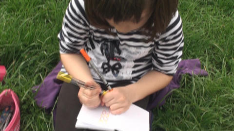 Little Girl Drawing On A White Paper In A Park, Na Footage