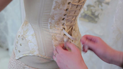 Woman tightens the laces on a corset Live Action