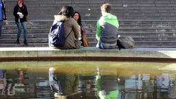 Couple sitting on the edge of fountain in front of Live Action