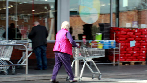 Panning an elderly woman with a shopping trolley Footage