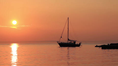 Sailing boat under a ruddy peach sunset sky 1 Footage