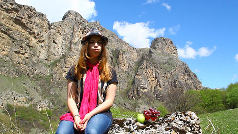 Young Girl Sitting On A Rock And Eating Fruit In N stock footage
