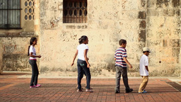 Kids playing ball aginst church wall Footage