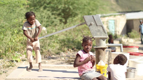 Little girl pumping water at well Live Action