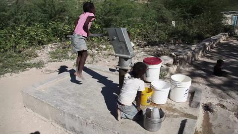 Kids pumping water at well glidecam shot Live Action