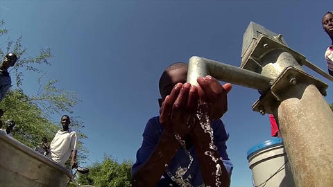 Boy drinking water from well slow motion Live Action