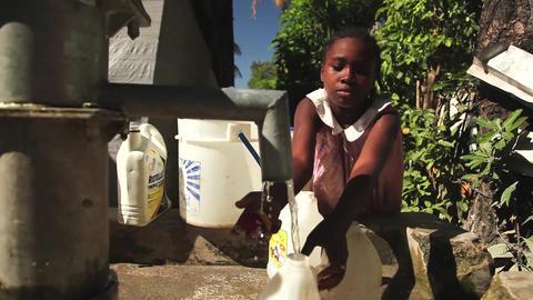 Girl filling jug at well dolly shot Live Action