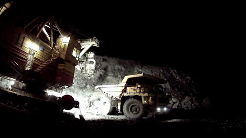 The excavator loads dump truck. Night mode Footage