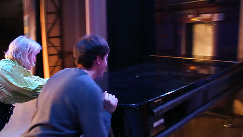 Man and woman move the piano on the stage of the t Footage