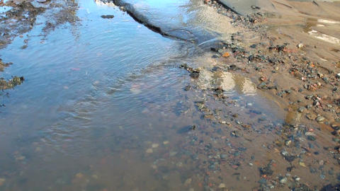 Water flows out from under the asphalt. The accide Footage