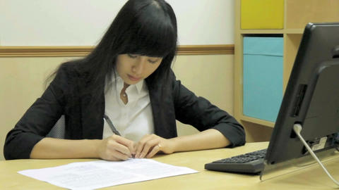 Asian Businesswoman Sitting Writing At An Office D stock footage