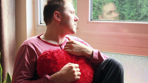 Romantic guy sitting sad with heart-shaped cushion Footage