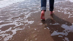 slim girl in jeans goes barefoot on the beach Footage