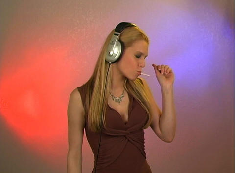Beautiful Blonde with Headphones and a Lolly Pop Footage