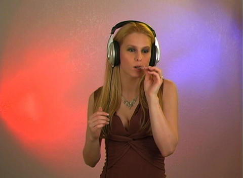 Beautiful Blonde with Headphones and a Lolly Pop Stock Video Footage