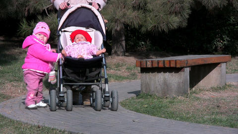 baby with toy doll in pram Footage