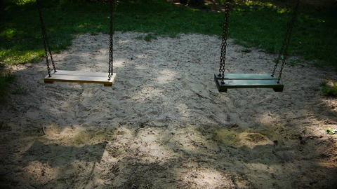 Two empty swings in a playground Footage
