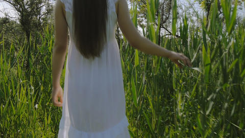 Girl in white dress walking through the grass Footage