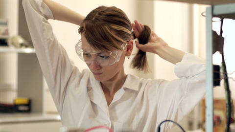 Girl Assistant in Laboratory Straightens Hair Footage