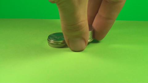 Hand Putting Stacks Of Coins On A Green Screen, Cu Footage