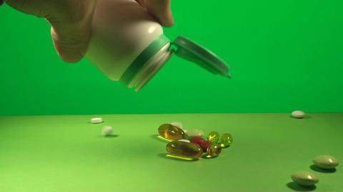 Hand Pouring The Content Of A Pill Bottle On A Gre stock footage