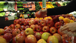 Woman selecting fresh red apples in grocery store Footage