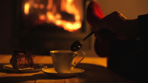 Man relaxes by warm fire then stirs drink with tea Footage