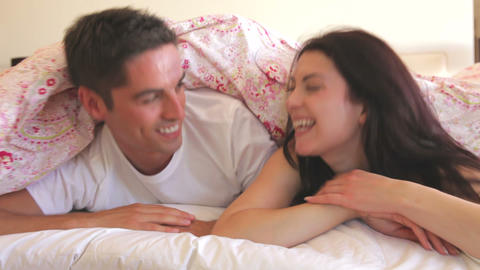 Couple hiding under duvet on bed before pulling it Footage