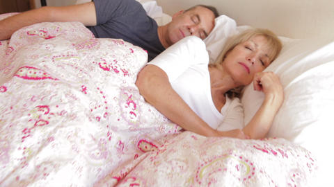 Camera Tracks Along Bed To Sleeping Senior Couple  stock footage
